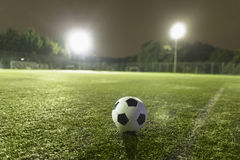 Soccer ball on sports field at night Stock Image