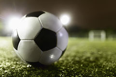 Soccer ball on sports field at night Stock Photo