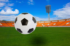 Soccer ball on stadium. Black and white soccer ball flying over football field on football stadium stock photos