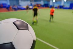 Soccer Ball on Stadium and football players defocused in field. Background Royalty Free Stock Images