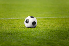 The Soccer Ball On Stadium Green Field. Football Pitch in the Background. Traditional Soccer Ball on the Pitch Royalty Free Stock Photo
