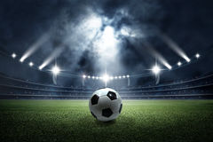 Soccer ball in the stadium. The imaginary football stadium is modeled and rendered royalty free stock photo