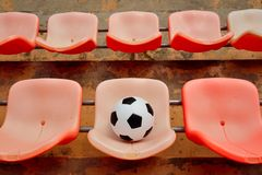 Soccer ball on stadium seat Royalty Free Stock Image