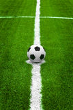 Soccer ball on start point center of field Stock Image