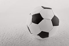 The soccer ball on the textured armadillo like ground Stock Photo