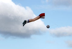 Soccer ball about to be kicked kite. Kite flown on windy day shaped like a soccer player with a ball Royalty Free Stock Photography