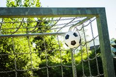 Soccer ball in top corner of the goal in summer stock photography