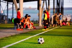 Soccer ball at touchlines on artificial turf with blurry of soccer players stock image