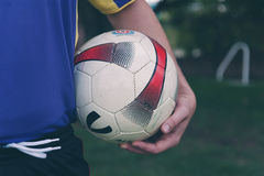 Soccer ball under player's arm Stock Photos