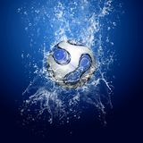 Soccer ball under water. Water drops around soccer ball under water on blue background royalty free stock photos