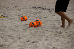 Soccer balls on beach. Feet of man playing with orange and black soccer balls on sandy beach Stock Images