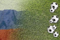 Soccer balls on green lawn with Russian flag Stock Photos