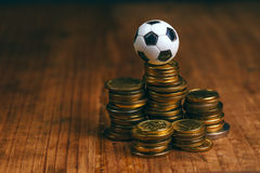 Soccer bet concept with football and money. Soccer bet concept with small football on top of coin stack, making money by predicting sport results stock photo