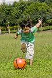 Soccer boy. Picture of a little chinese boy playing soccer on lawn in a sunny autumn day Stock Image