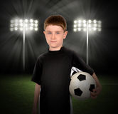 Soccer Boy Holding Ball in Stadium. A young boy is holding a soccer ball with a stadium of lights in the background at night for a game or sport concept Royalty Free Stock Images