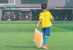 Soccer Boy training alone with cone on training ground. Soccer Boy is training alone with cone on training ground royalty free stock photos