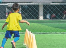 Soccer Boy training alone with cone on training ground royalty free stock image