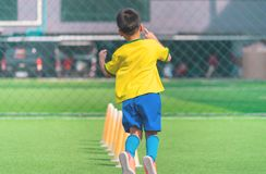 Soccer Boy training alone with cone on training ground. Soccer Boy is training alone with cone on training ground royalty free stock image