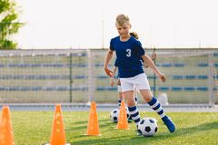 Soccer camp for kids. Boys practice dribbling in a field. Players develop good soccer dribbling skills. Children training with balls and cones. Soccer slalom royalty free stock images
