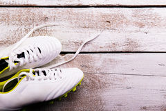 Soccer cleats against wooden background. Studio shot. Copy space. Royalty Free Stock Images