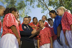 Soccer Coach Discussing Strategy With Girls Team. Low angle view of soccer coach discussing strategy with girls team Stock Photography