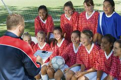 Soccer Coach Explaining Strategy To Team. Mature male soccer coach explaining strategy to team during time out Royalty Free Stock Images