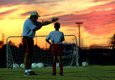 Soccer coaching at sunset. A coach giving instructions to a soccer player under a red sunset sky royalty free stock photography