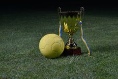Soccer cup. Golden soccer cup and ball on grass field stock photo