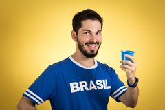 Supporter of National Team of football is toasting, cheers. Soccer fan in action emotions, happy. Supporter of brazil National Team of football is toasting Royalty Free Stock Photos