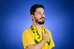 Brazilian supporter of National Team of football is listening to. Soccer fan in action emotions: respect, pride. Supporter of Brazil National Team of football is royalty free stock image