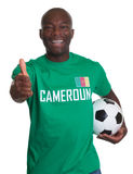 Soccer fan from Cameroon with Football showing thumb up. On an isolated white background for cutout stock image