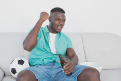 Soccer fan cheering while watching tv. Concentrated soccer fan cheering while watching tv Stock Image