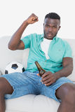 Soccer fan cheering while watching tv. Portrait of soccer fan cheering while watching tv Royalty Free Stock Images