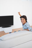 Soccer fan cheering while watching tv. Portrait of a soccer fan cheering while watching tv Stock Photography
