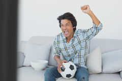 Soccer fan cheering while watching tv. Portrait of a happy soccer fan cheering while watching tv Stock Image