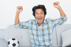 Soccer fan cheering while watching tv. Portrait of a happy soccer fan cheering while watching tv Royalty Free Stock Photos