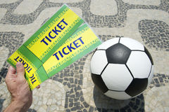 Soccer fan holds tickets above football in Brazil Royalty Free Stock Photos