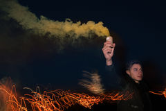 Soccer fan with smoke bomb. Rowdy guy with protest sign in hand on night lights background Royalty Free Stock Photo