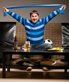 Soccer fan on sofa Royalty Free Stock Image