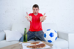 Soccer fan in team jersey watching football game on TV at home couch gesturing disappointed Royalty Free Stock Photo