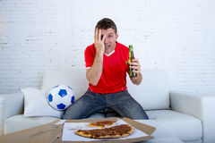 Soccer fan in team jersey watching football game on TV nervous and stressed. Young soccer supporter man wearing team jersey holding beer bottle watching football Royalty Free Stock Photos