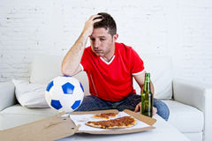 Soccer fan watching football game on TV sad disappointed and desperate Stock Image