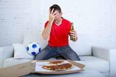 Soccer fan watching football game on TV sad disappointed and desperate Royalty Free Stock Image