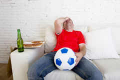 Soccer fan watching football game on TV sad disappointed leaning on couch hopeless Stock Images