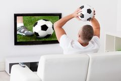 Soccer fan watching a game. Excited soccer fan watching a game on television Royalty Free Stock Photo