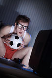Soccer Fan Watching Television. Young man soccer fanatic getting really into the soccer game on television Stock Photo