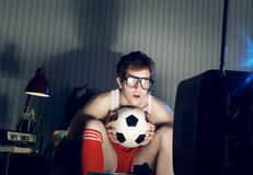 Soccer Fan Watching Television. Young man soccer fanatic watching soccer match in television Royalty Free Stock Photography