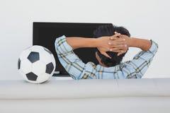 Soccer fan watching tv. Rear view of a soccer fan watching tv Royalty Free Stock Photos
