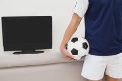 Soccer fan watching tv. Rear view of a soccer fan watching tv Stock Image