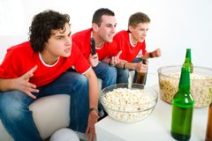 Soccer fans. Three exciting men sitting on couch and watching sport on TV Stock Photography